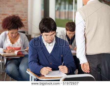 Group of students giving exam while teacher supervising them in classroom
