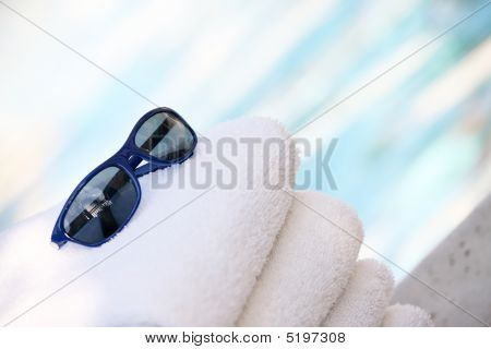 Towels And Sunglasses By Pool