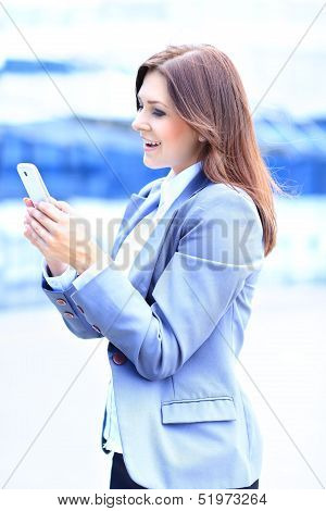 Smiling businesswoman using the mobile phone