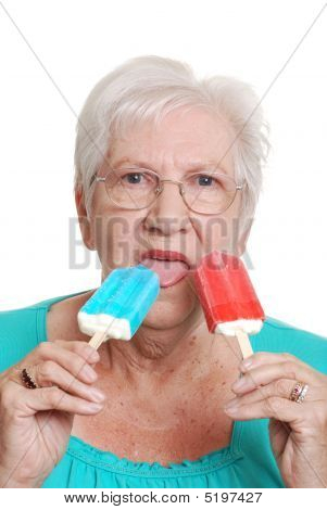 Senior Woman Eating Red And Blue Popsicles