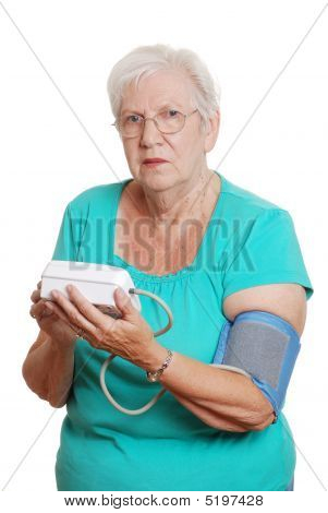 Senior Woman Using Automatic Blood Pressure Machine
