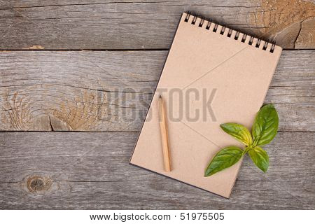 Blank notepad for copy space and basil leaves on wooden table