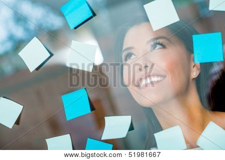 Woman multitasking with posting post-its all over the place
