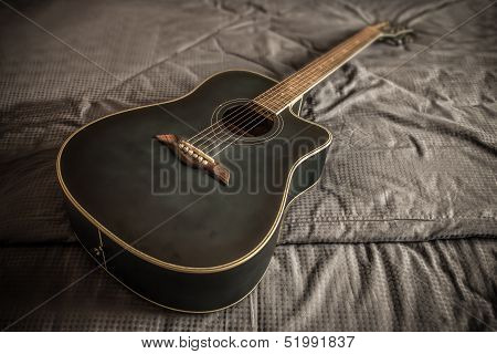 Old Dusty Acoustic Cutaway Guitar In Bed In A Daken Bedroom