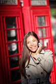 image of phone-booth  - London woman taking on smartphone by red phone booth - JPG
