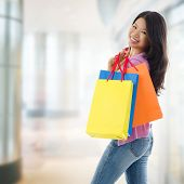 stock photo of southeast  - Happy Asian shopping woman smiling holding many shopping bags at the mall - JPG