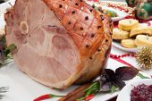 picture of christmas meal  - Roasted spiced ham on holiday dinning table garnished with cloves cinnamon sticks hot chili pepper and purple basil - JPG