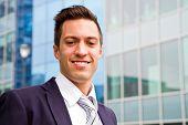 pic of youg  - smiling youg businessman standing in front og building - JPG