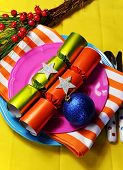 foto of christmas meal  - Bright and colorful Christmas table setting with plates forks and knives Christmas Bon Bons Crackers with decorations for a lively stylish and fun holiday party atmosphere - JPG