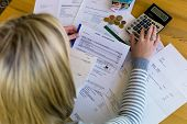 stock photo of budget  - a woman with unpaid bills has many debts - JPG