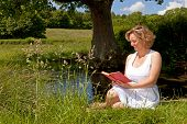 A woman in a white dress sat by a stream reading a book on a bright summers day.
