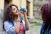 picture of two women taking cell phone  - Portrait of two young black girls taking pictures of themselves through cellphone - JPG