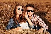 stock photo of independent woman  - Romantic young couple in casual clothes sitting together in haystack - JPG