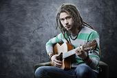 image of dreadlock  - Young man playing acoustic guitar - JPG