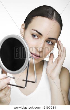 Jovem mulher olhando no espelho para verificar se ela compõem