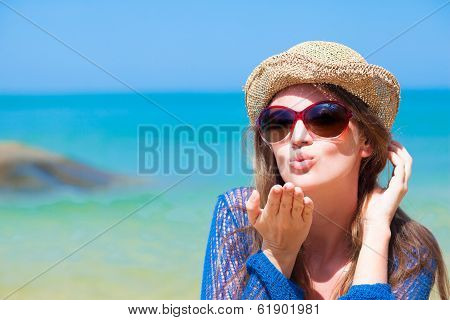 portrait of young woman in sunglasses and straw hat blowing an air kiss on beach
