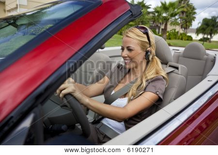 Beautiful Young Woman Driving Convertible Car Talking On Headset