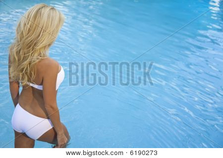 Beautiful Sexy Blond Woman In Bikini Walking Into Blue Pool
