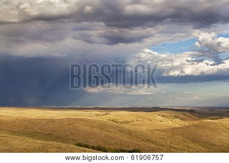 heavy storm clouds over a rolling prairie at foothills of Rocky Mountains in Colorado - Soapstone Prairie Natural Area near Fort Collins