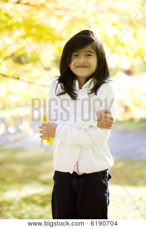 Little Biracial Asian Girl Standing Amongst Bright Autumn Leaves