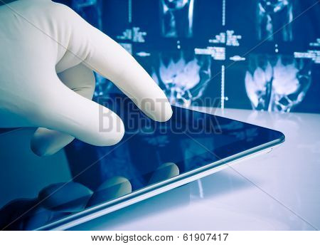 Hand In Medical Blue Glove Touching Modern Digital Tablet On X-ray Images Background