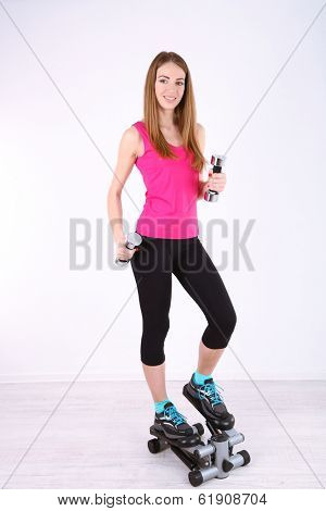 Young beautiful fitness girl exercising with dumbbells on stepper, in gym