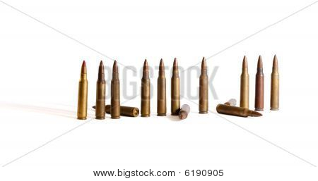 Row of standing M16 cartridges with some fallen isolated