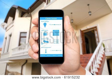 Male Hand Hold A Phone With System Clever House On The Background Of The House