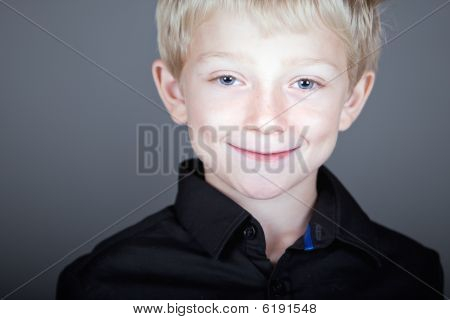 Sweet Blonde Haired Child Against Grey Background