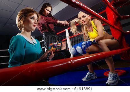 Boxing Woman in box gloves sitting on ring and surrounded by Visagiste and Hairdresser