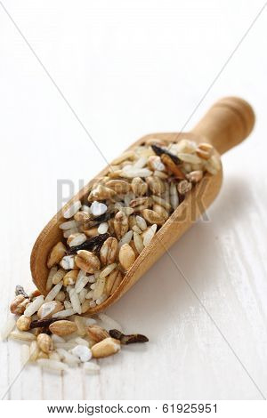 Uncooked Multigrain Rice In Wooden Scoop On White Wooden Background