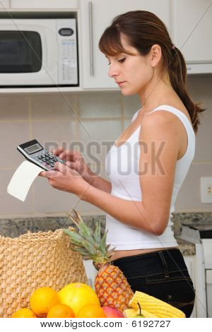 Woman Checking Bill With Calculator In The Kitchen