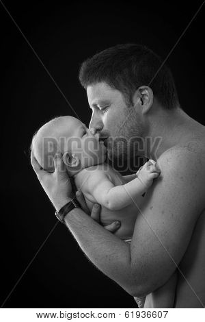 Black and white photo of father holding and kissing newborn baby, semi-nude, side view.