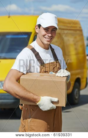Smiling young male postal delivery courier man in front of cargo van delivering package