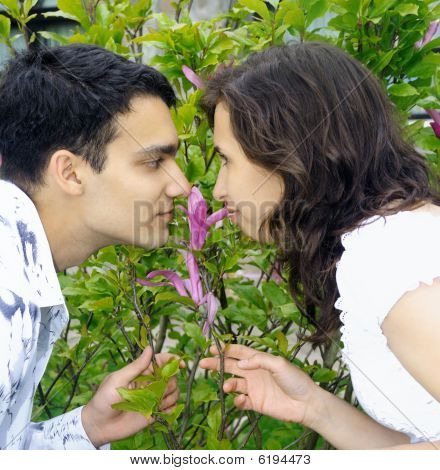 Beautiful Young Couple Outdoors Smells A Flower
