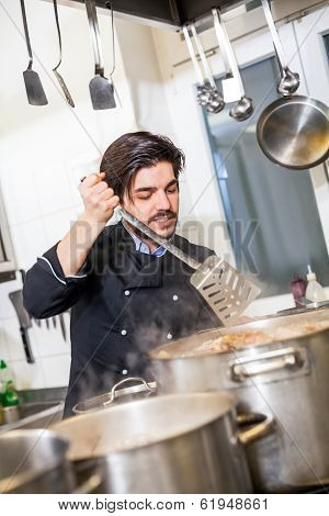 Chef Stirring A Huge Pot Of Stew Or Casserole