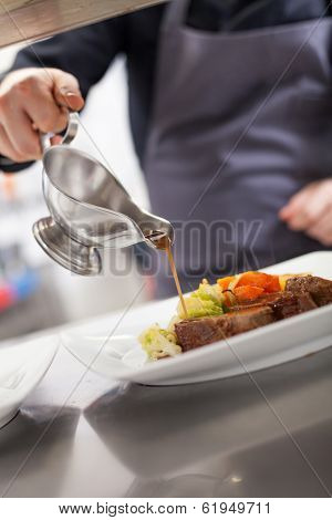 Chef Plating Up Food In A Restaurant