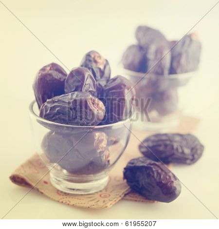 Dried date palm fruits or kurma, ramadan food which eaten in fasting month in vintage retro effect.