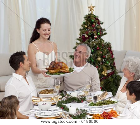 Woman Showing Turkey To Her Family For Christmas