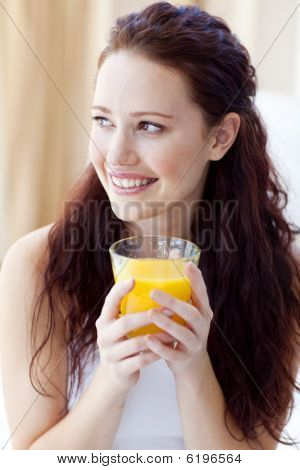 Portrait Of Woman Drinking Orange Juice In Bedroom
