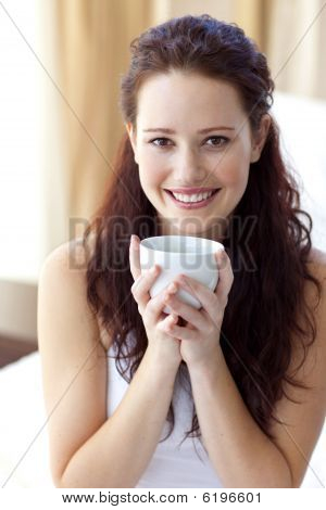 Beautiful Woman Drinking A Cup Of Coffee In Bedroom