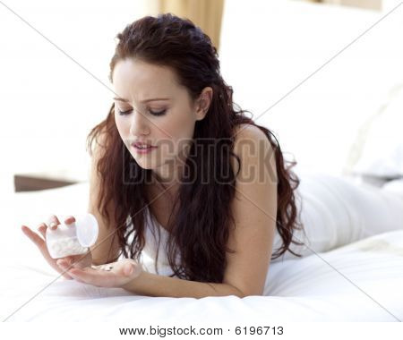 Worried Woman In Bed Taking Pills