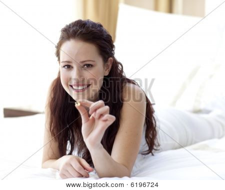 Beautiful Woman In Bed Holding A Pill