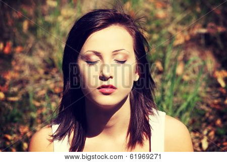 Face of young woman on meadow in park who is relaxed pose and performing meditation session. Brunette girl with close eyes and concentrated face expression.