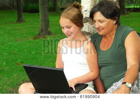 Grandmother and granddaughter sitting outside with laptop computer