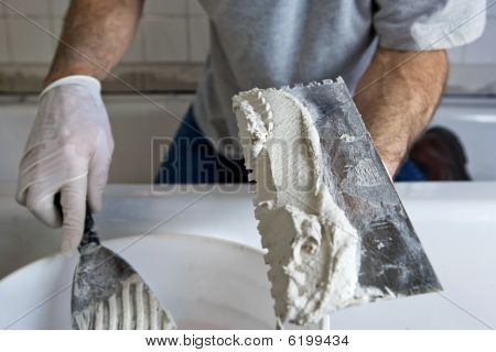 Man Working With Trowel And Mortar Tiling A Bathroom Wall