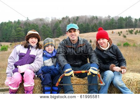 Family sitting on a vagon on Christmas tree farm