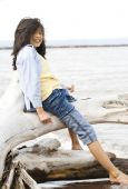 picture of young girls  - Little girl playing on fallen tree by lake shore in summer - JPG
