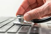 image of check  - Conceptual image of the hand of a man checking the health of his laptop computer using a stethoscope as he checks for malware and viruses or any electronic malfunctions.