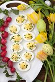 stock photo of radish  - Plate of deviled eggs fresh radish Easter decoration eggs and fresh spring blooming tulips - JPG